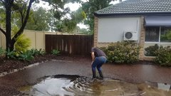 Thumbnail of Plumber clearing a blocked grate after storm